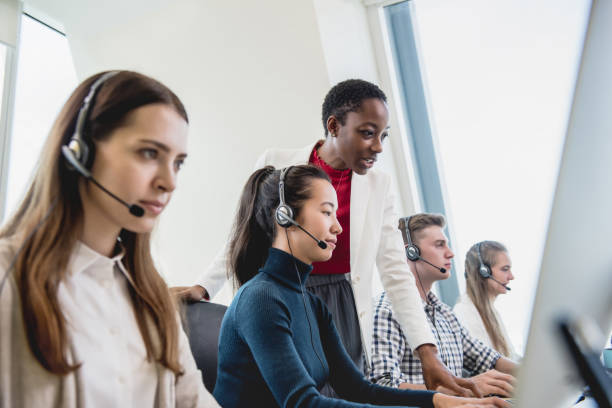 Female supervisor working with team in call center stock photo