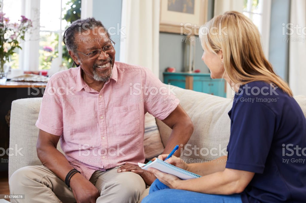 Female Support Worker Visits Senior Man At Home stock photo