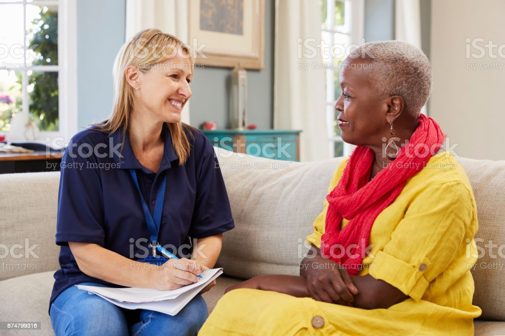 Female Support Worker Visits Senior Woman At Home stock photo