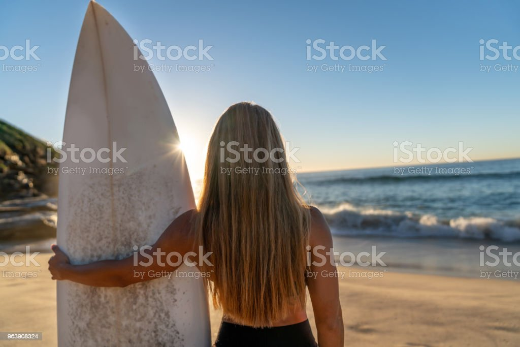 Female surfer carrying her board and watching the sunrise - Royalty-free Adults Only Stock Photo