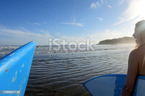 istock Female surfer heads out for morning session with friend following 1293632132