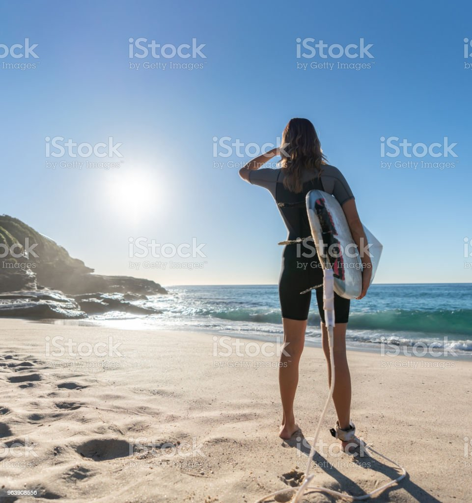 Female surfer holding a surfboard at the beach - Royalty-free Adult Stock Photo