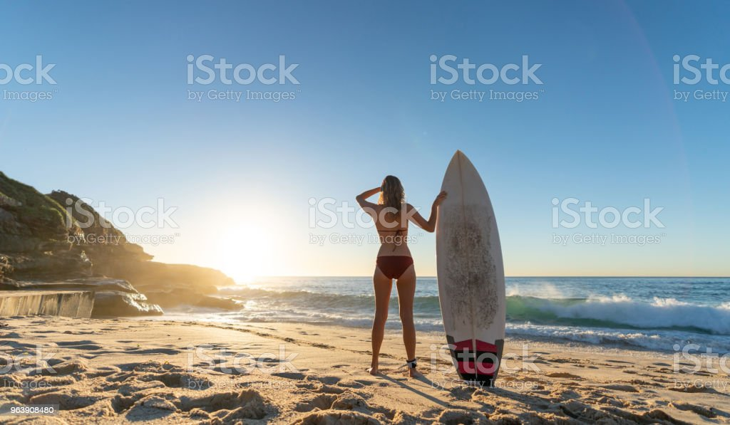 Female surfer holding her board and watching the sunrise - Royalty-free Adult Stock Photo