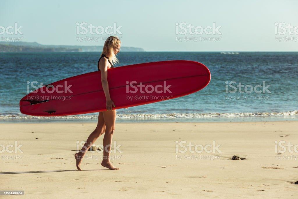 female surfer holding surfboard and walking on beach near the sea - Zbiór zdjęć royalty-free (Deska surfingowa)