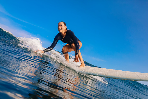istock Female surfer on a blue wave 1213440675
