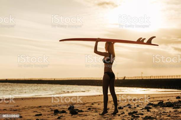 Kobieta Surfer Pozowanie Z Deską Surfingową Na Głowie O Zachodzie Słońca - zdjęcia stockowe i więcej obrazów Deska surfingowa