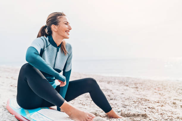 Female surfer resting on the beach Smiling female surfer sitting on the beach wetsuit stock pictures, royalty-free photos & images