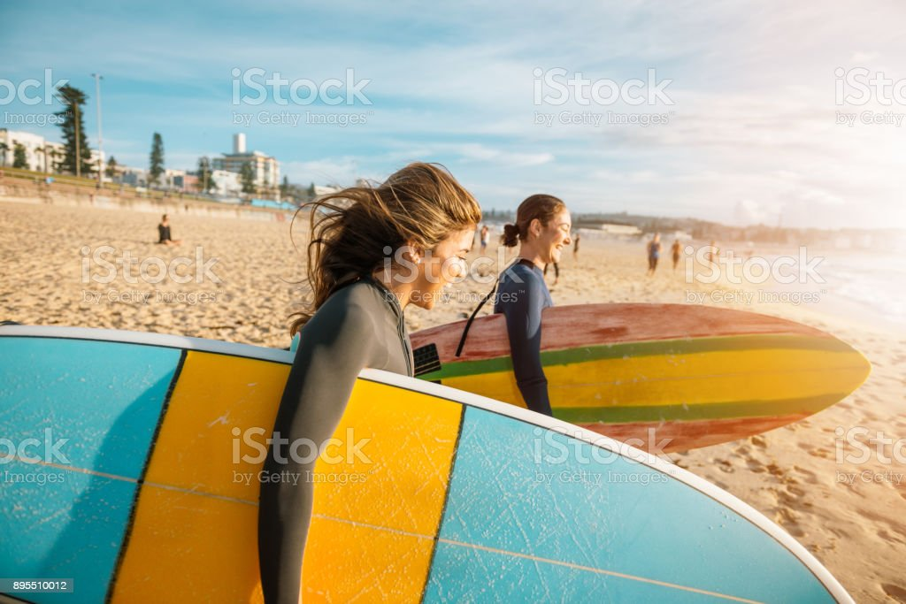 Female surfers rushing to catch a waves stock photo
