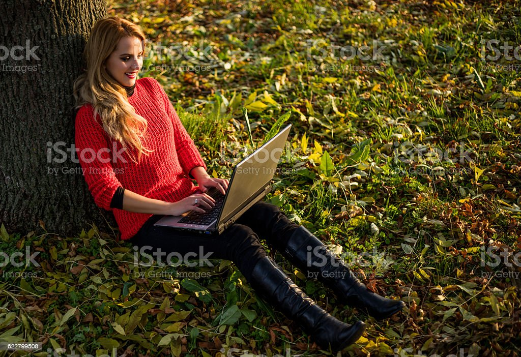 Female surfing internet on sunny day. stock photo