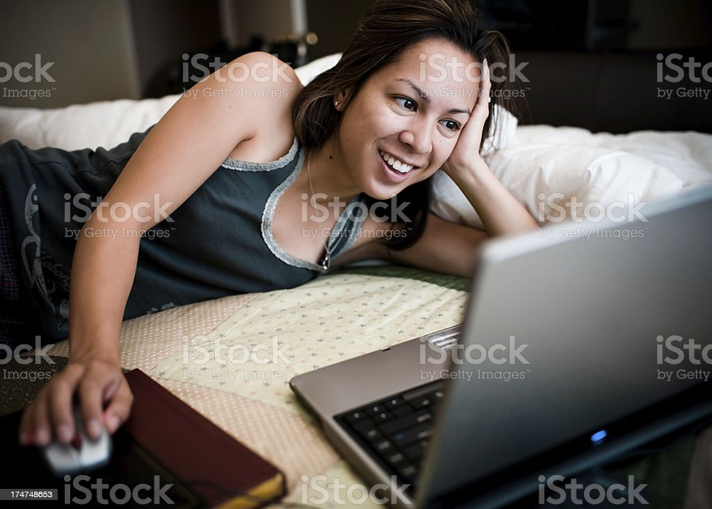 female surfing the web on her bed royalty-free stock photo