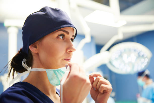 Female surgeon preparing for the operation Female surgeon preparing for the operation surgical cap stock pictures, royalty-free photos & images