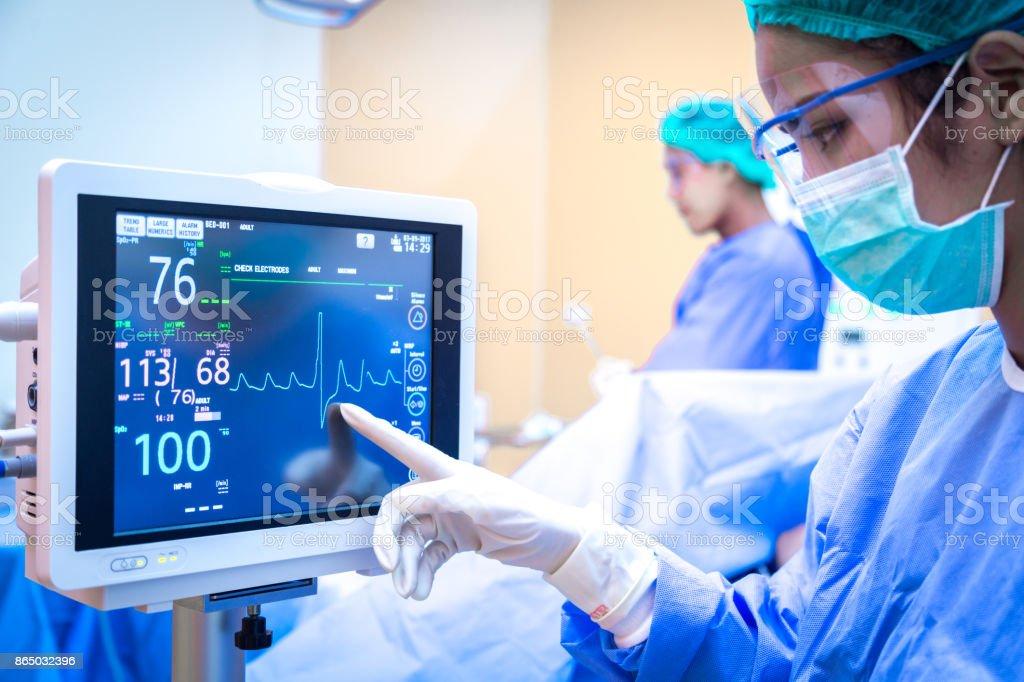 Cirurgiã usando monitor na sala de cirurgia. - foto de acervo