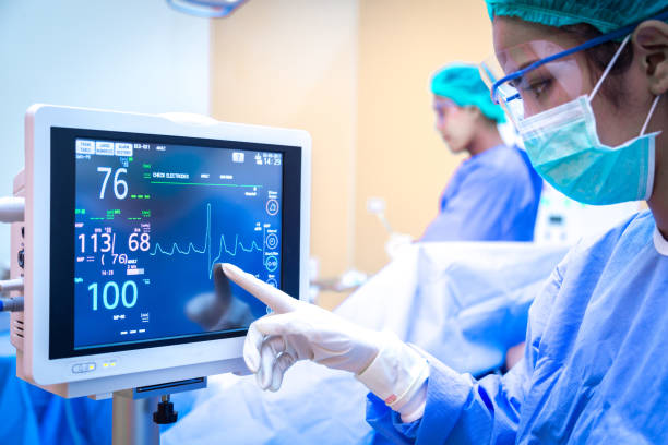 Female surgeon using monitor in operating room. Female surgeon using monitor in operating room. life support machine stock pictures, royalty-free photos & images