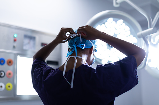 istock Female surgeon wearing surgical mask in operation theater at hospital 1155608121