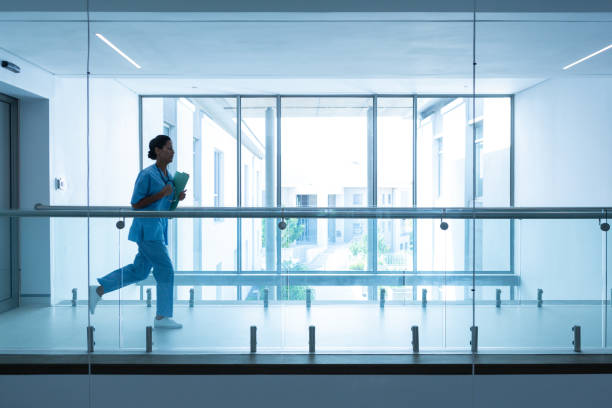 Female surgeon with medical reports running in corridor at hospital stock photo