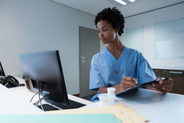 Female surgeon writing on clipboard while working on computer at desk stock photo