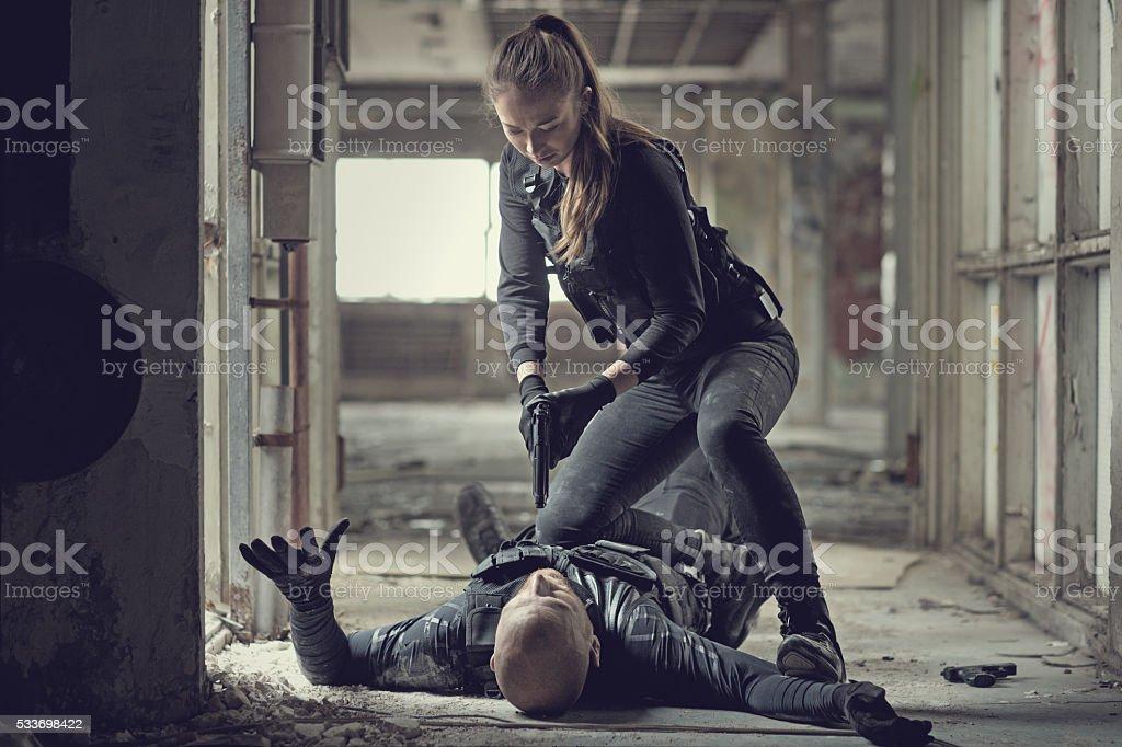 Female swat team member arresting male insurgent at gunpoint stock photo