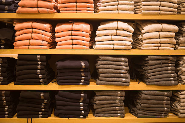 female  sweater stack in the shelf in the retail market - fleecepullover stock-fotos und bilder