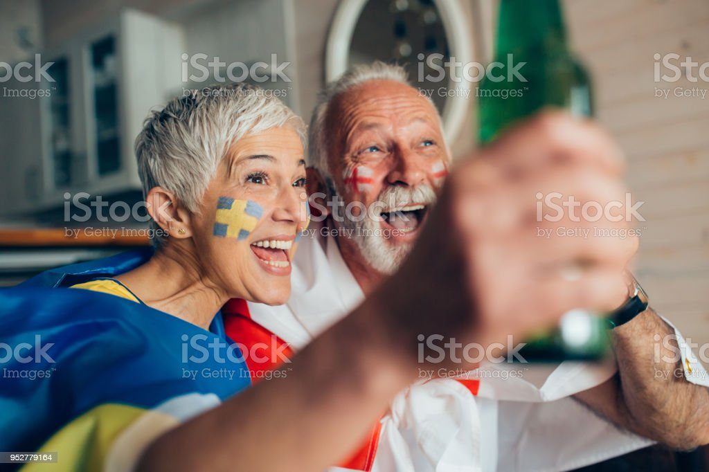 Mature couple watching soccer and drinking beer