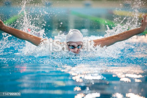 Young woman at the swimming competition in an olympic size swimming pool. Butterfly stroke.