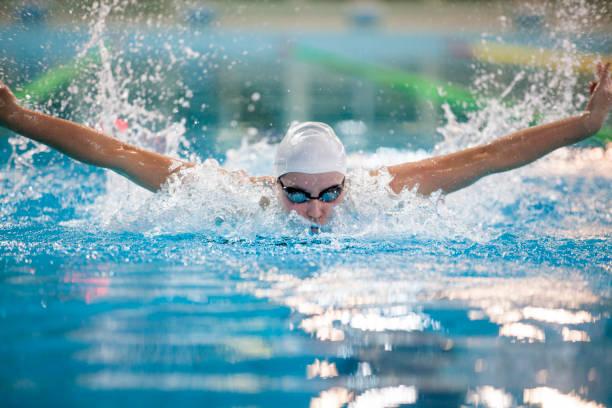 vrouwelijke zwemmer-butterfly stroke - wedstrijdsport stockfoto's en -beelden