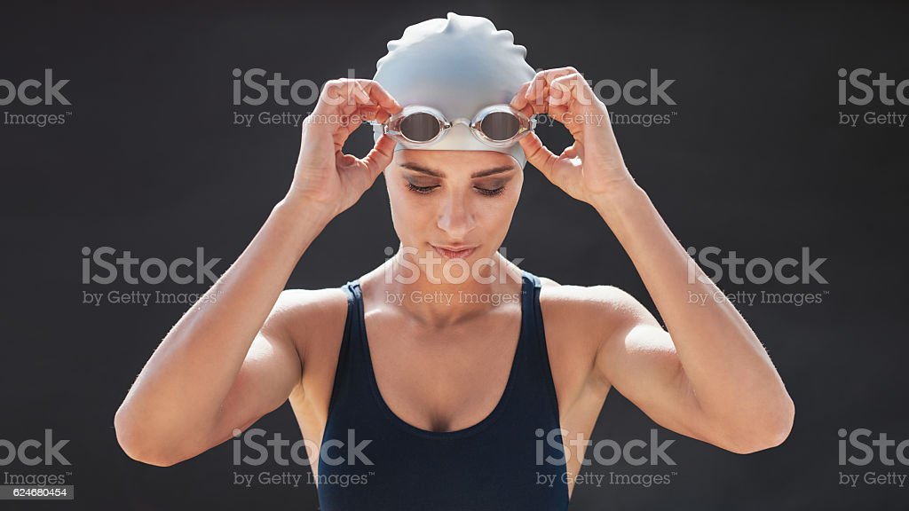 Female swimmer in a swimsuit adjusting her goggles – Foto