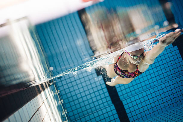 female swimmer in action inside swimming pool - vuelta completa fotografías e imágenes de stock
