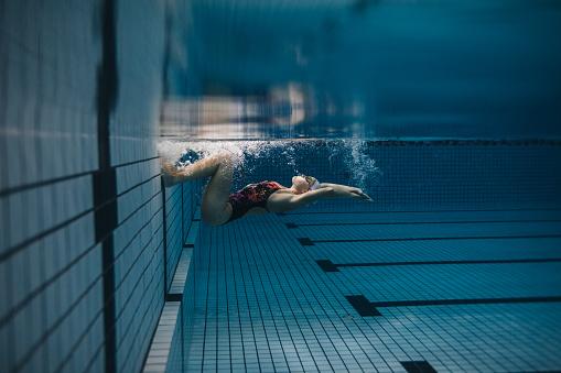 Female swimmer in action inside swimming pool