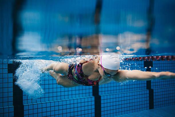 female swimmer in action inside swimming pool. - vuelta completa fotografías e imágenes de stock