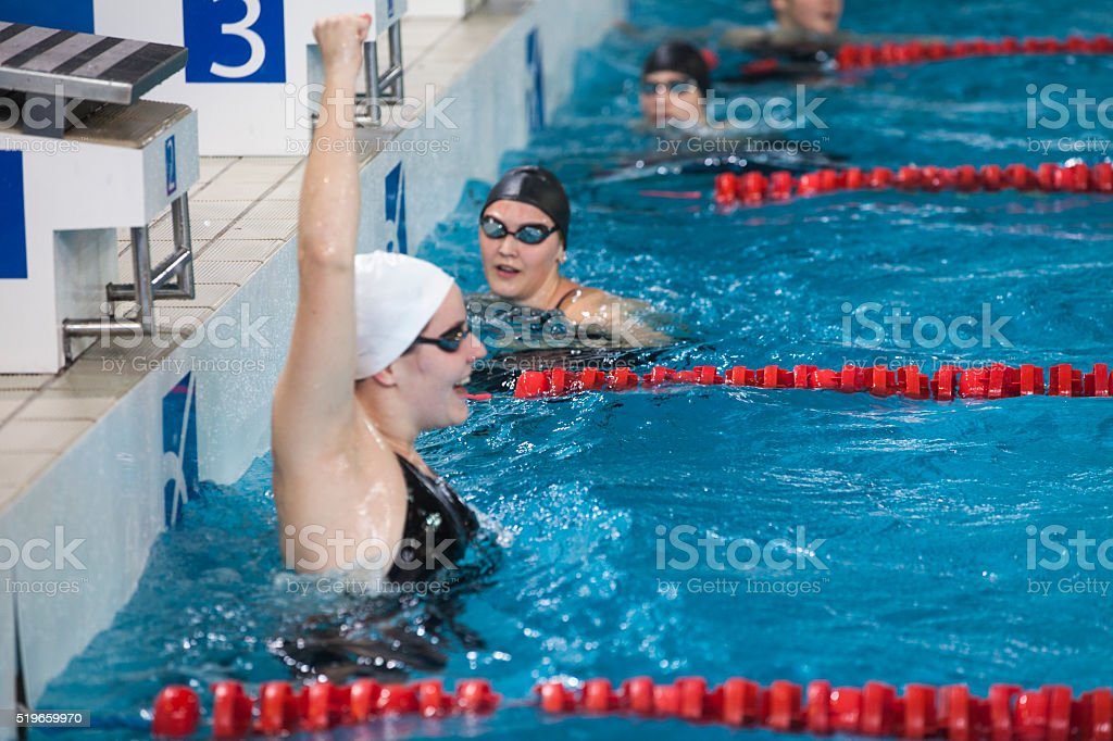 Female swimmer cheering in swimming pool during swimming competition.
