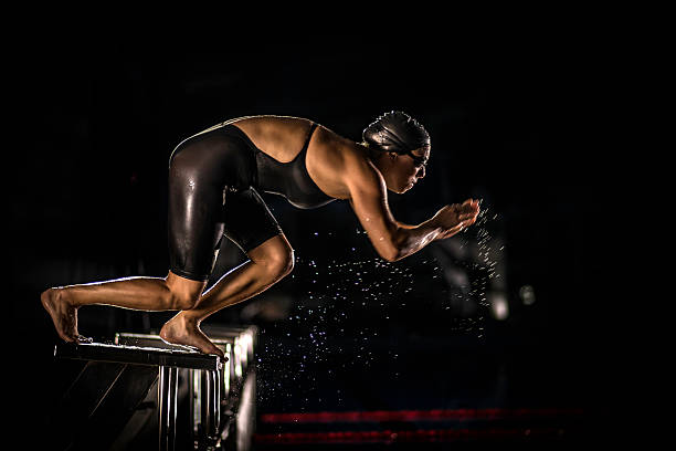 Female Swimmer Jumping Off The Starting Block stock photo