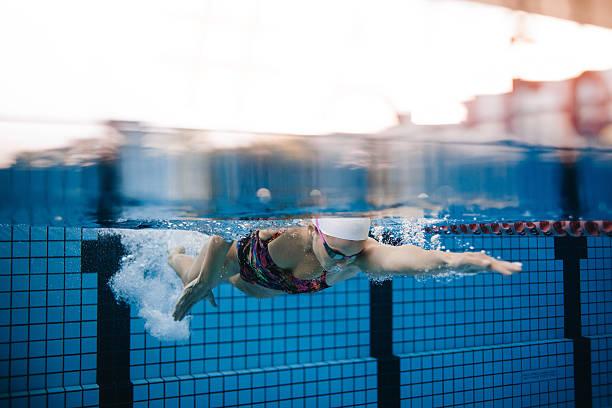 female swimmer training in the swimming pool - vuelta completa fotografías e imágenes de stock