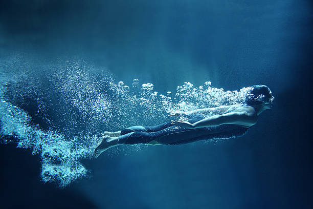 Female swimmer underwater flowing on blue background Athlete is dressed in a professional black swimwear. She is swimming horizontally like she was flying. She has two hands together along the body. She is looking ahead.  Behind her body you can see a lot of air bubbles. The background is dark blue- like open water. underwater diving stock pictures, royalty-free photos & images