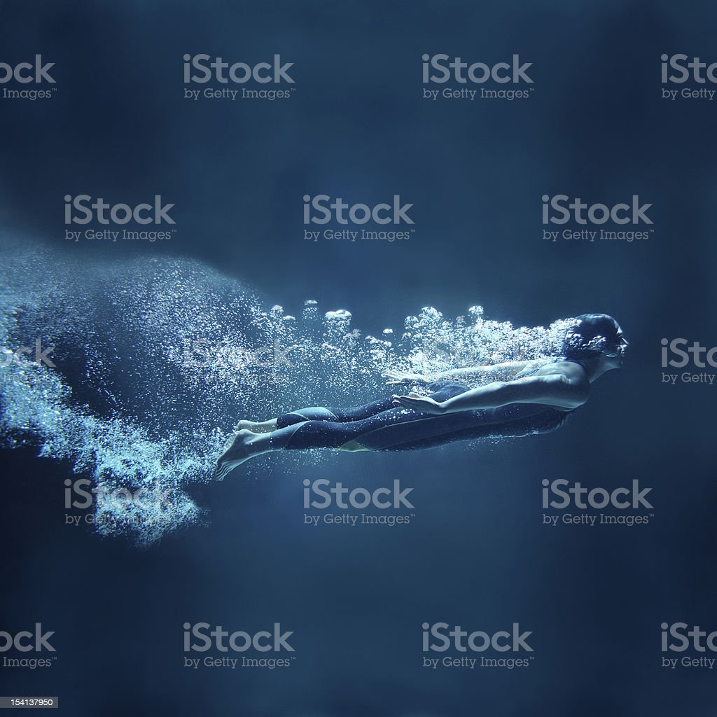 Female swimmer underwater flowing on blue background royalty-free stock photo