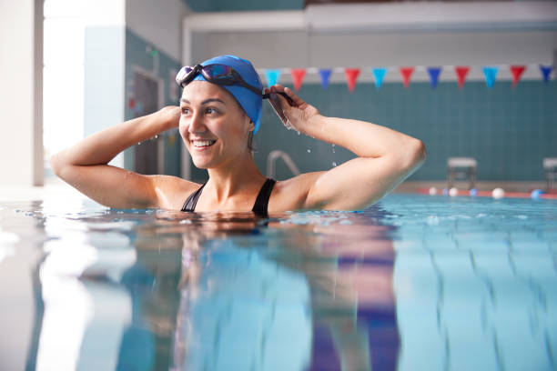 nadadora femenina usando sombrero y gafas de entrenamiento en la piscina - natación fotografías e imágenes de stock