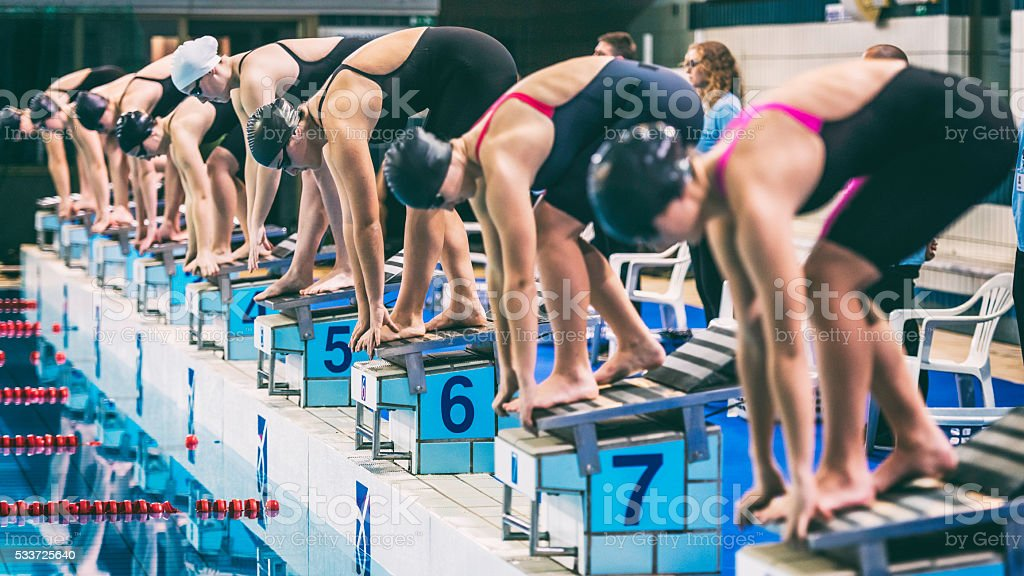 Female swimmers crouching on starting block ready to jump stock photo