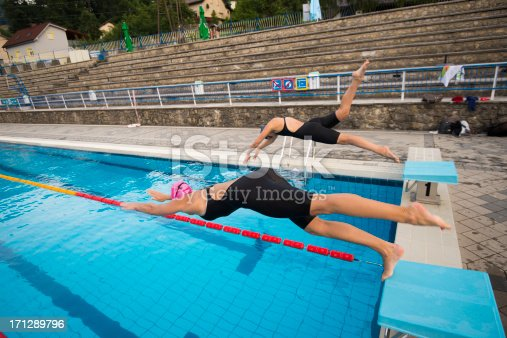 177281231 istock photo Female swimmers diving 171289796