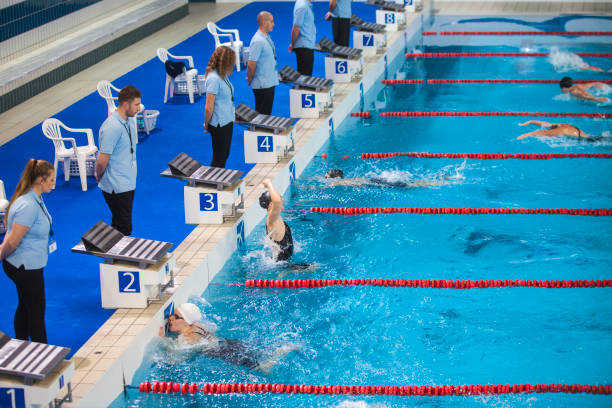 female swimming competition, butterfly stroke, winner celebrating - judge sports official stock photos and pictures