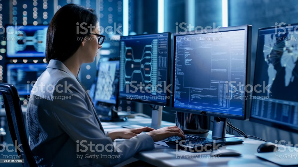 Female System Engineer Controls Operational Proceedings. In the Background Working Monitors Show Various Information. stock photo