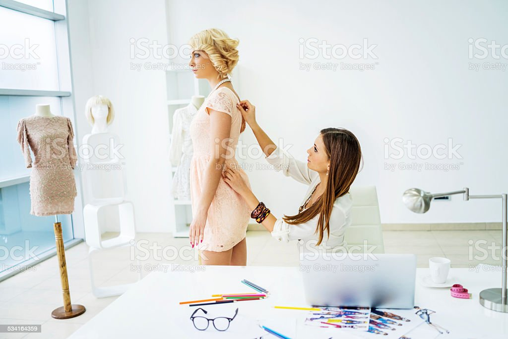 Female tailor taking measurements. stock photo