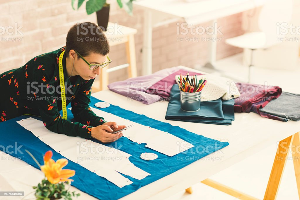 Female Tailor Using Phone In Her Workshop stock photo