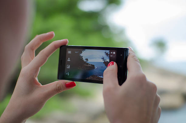 Female taking a photo with a mobile phone stock photo