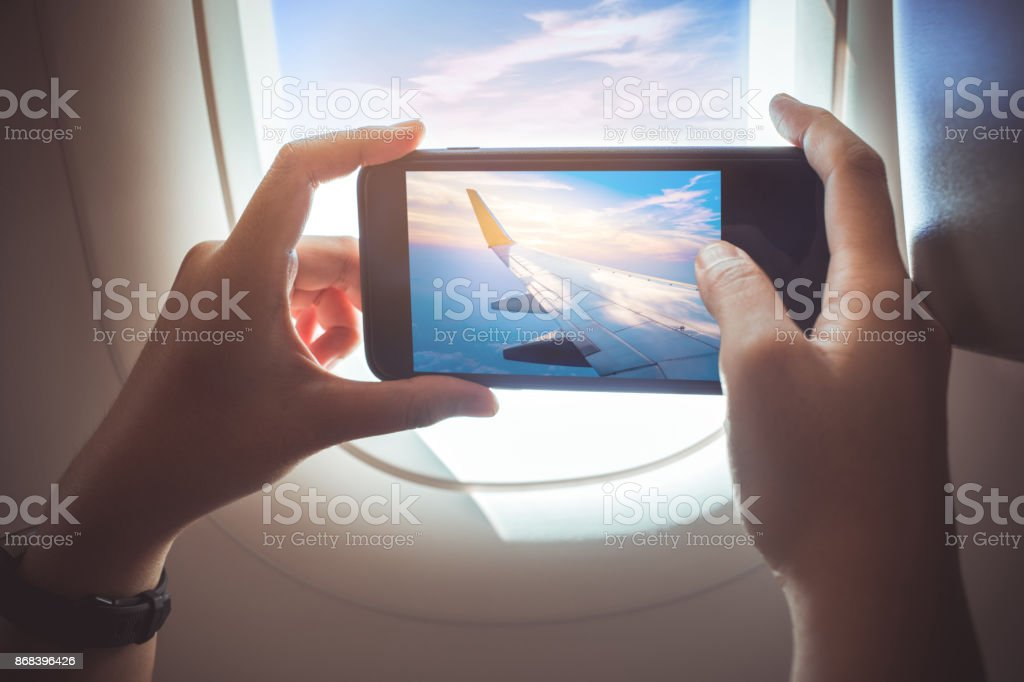 Female taking a photo with smartphone on plane. stock photo