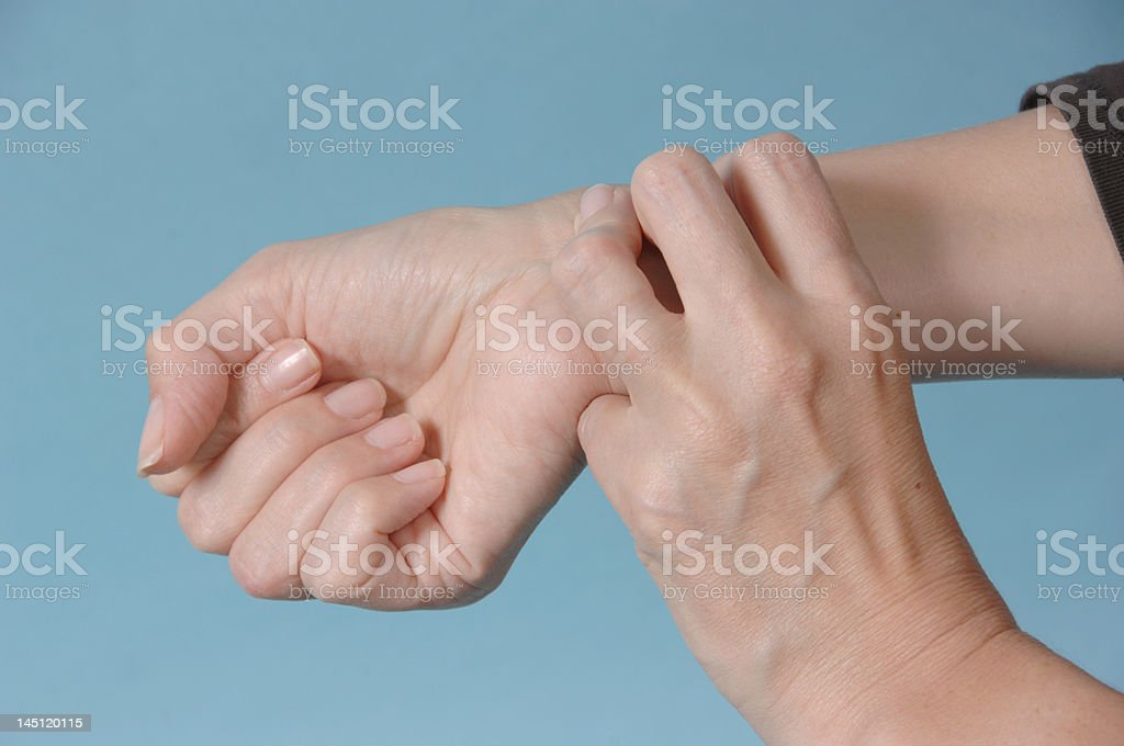 Female taking her own pulse against blue royalty-free stock photo