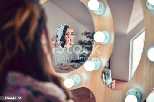 istock Female Taking Off Make Up In Front Of Mirror 1180300278