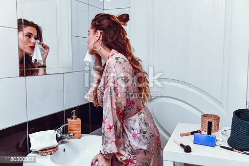 istock Female Taking Off Make Up In Front Of Mirror 1180300307