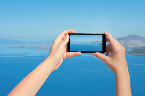 Female taking picture of landscape Greek island on mobile phone . Landscape of sea and mountain on smartphone