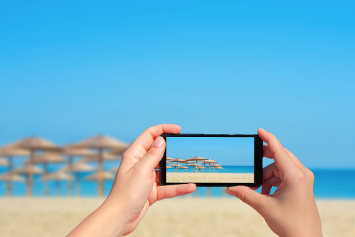 Female taking picture of tropical beach with big straw umbrellas on mobile phone.