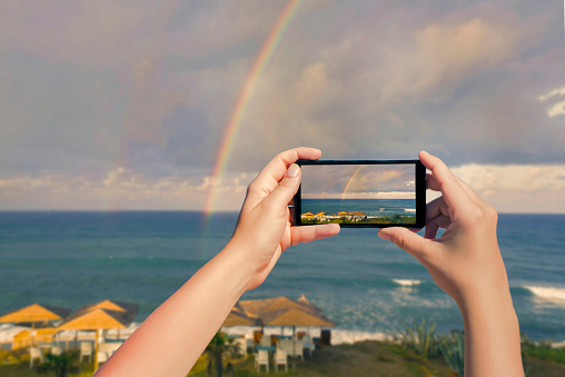Female taking picture on mobile phone of double rainbow over ocean and tropical beach with umbrellas chairs and tables. Landscape on  smartphone