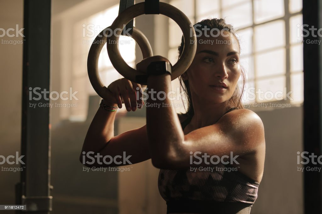 Female taking rest after dip ring workout stock photo